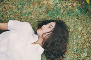dark haired girl lying down on the grass
